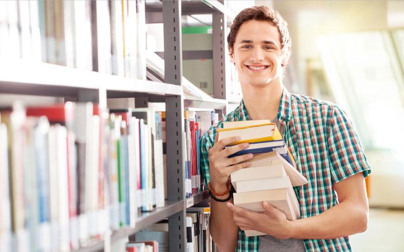 Student mit Büchern in Bibliothek